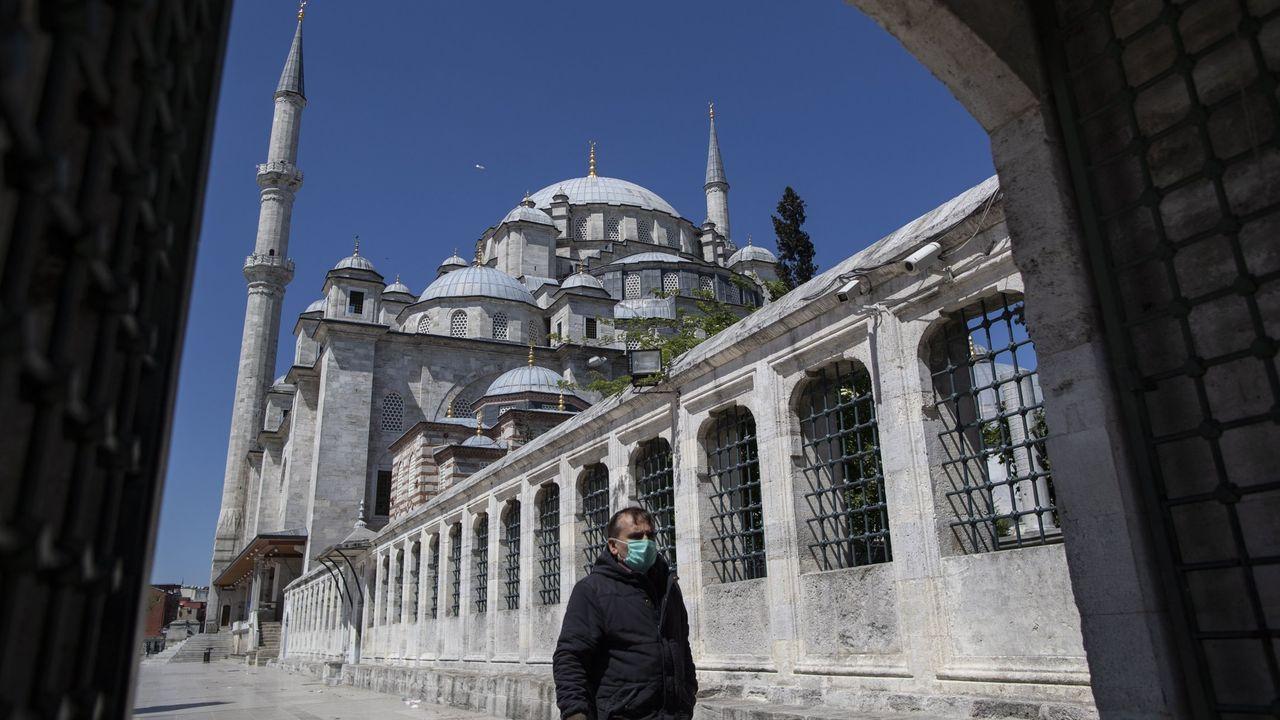 Un hombre con mascarilla pasea cerca de una mezquita en Estambul