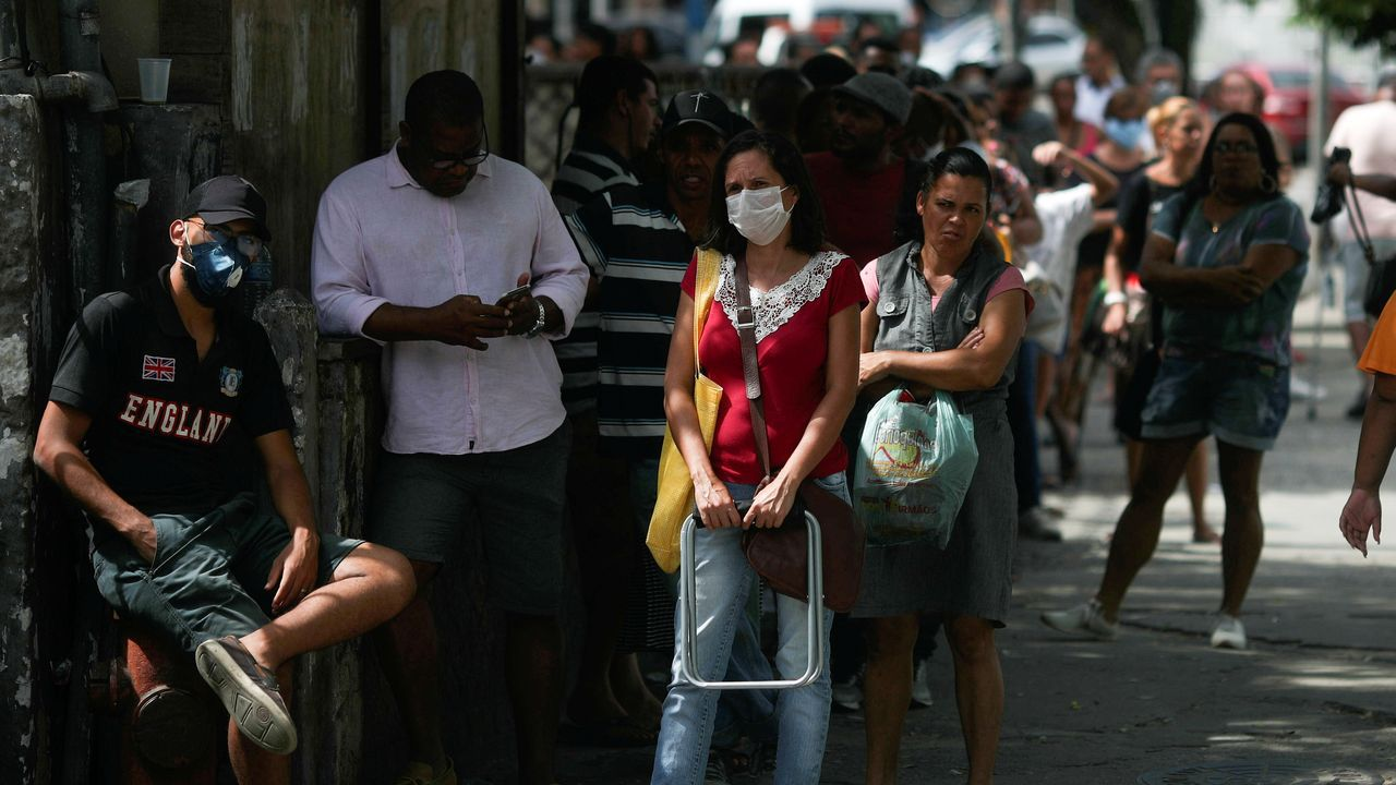 Habitantes de Río de Janeiro (Brasil) esperan en la fila a las puertas de un banco público, donde la mayoría de ellos acuden para recibir la ayuda de emergencia otorgada por el gobierno federal a los más vulnerables durante el brote de COVID-19