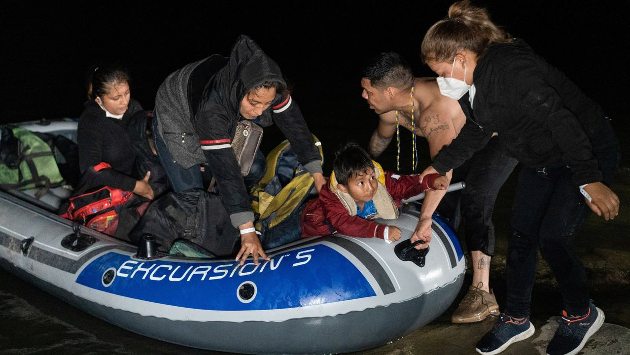 Inmigrantes desembarcan de un bote tras cruzar el río Grande a Texas desde México