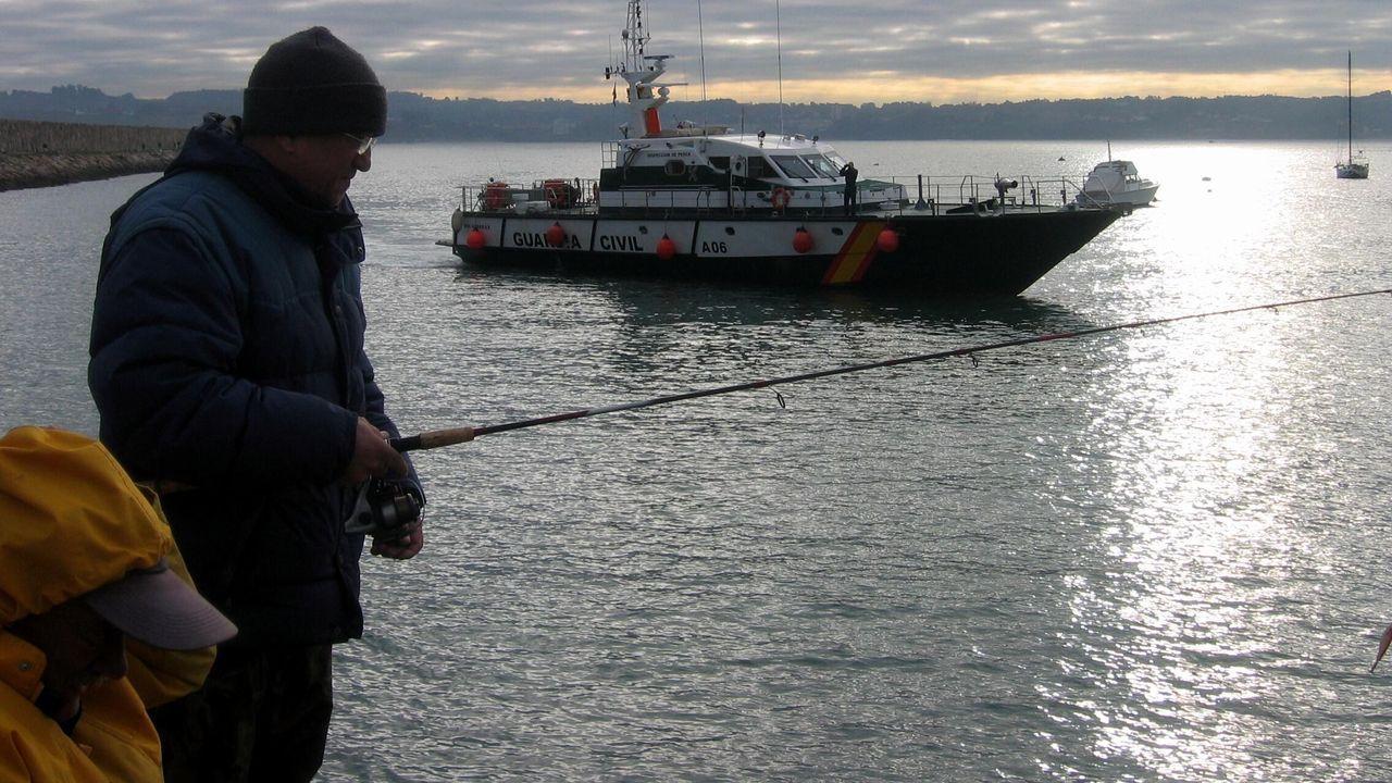 Pescadores recreativos practicando su afición en la costa gallega, con una patrullera de la Guardia Civil al fondo, en una imagen de archivo.
