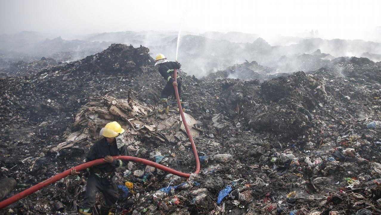 Un grupo de bomberos trata de extinguir un fuego en el vertedero de Htain Bin, en Rangún (Birmania)