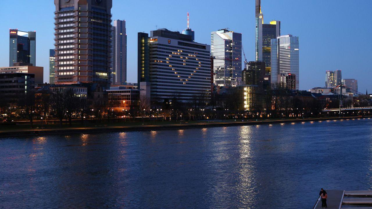Una pareja en un embarcadero frente al río Main, Fráncfort, justo delante de un edificio iluminado con un corazón