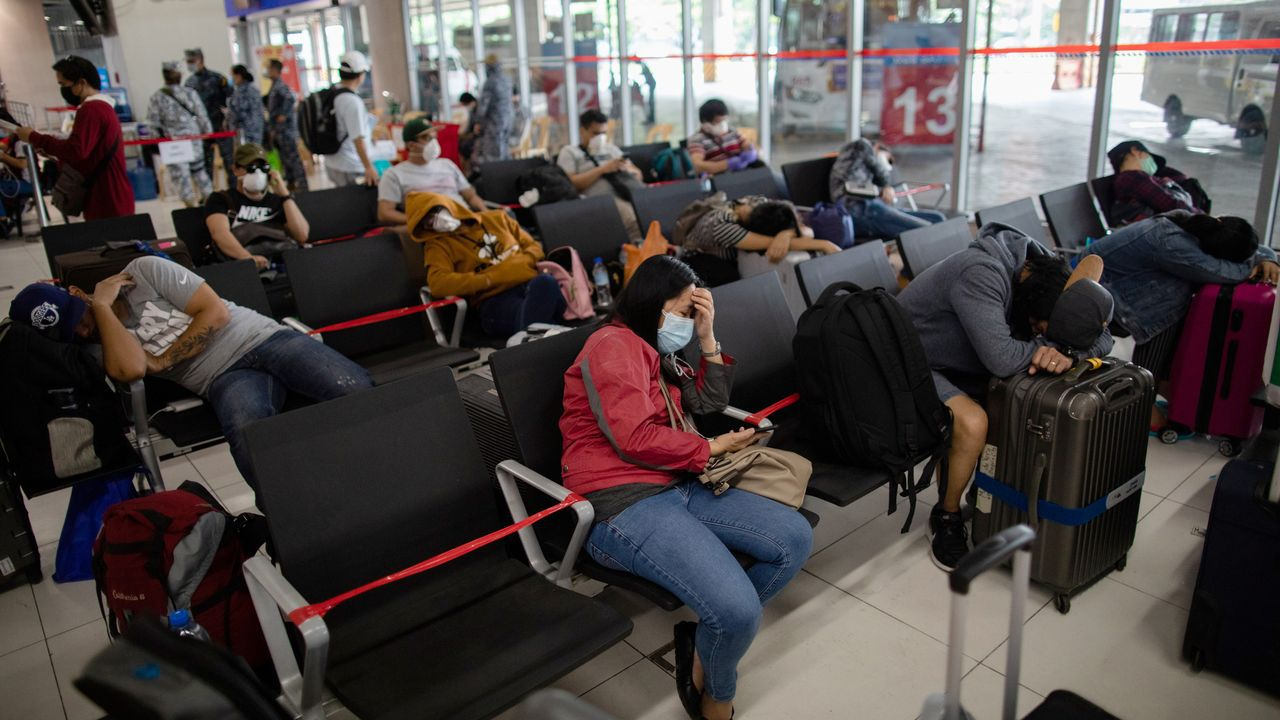 Filipinos repatriados que han cumplido con la cuarentena aguardan para tomar los autobuses que los llevarán a sus casas