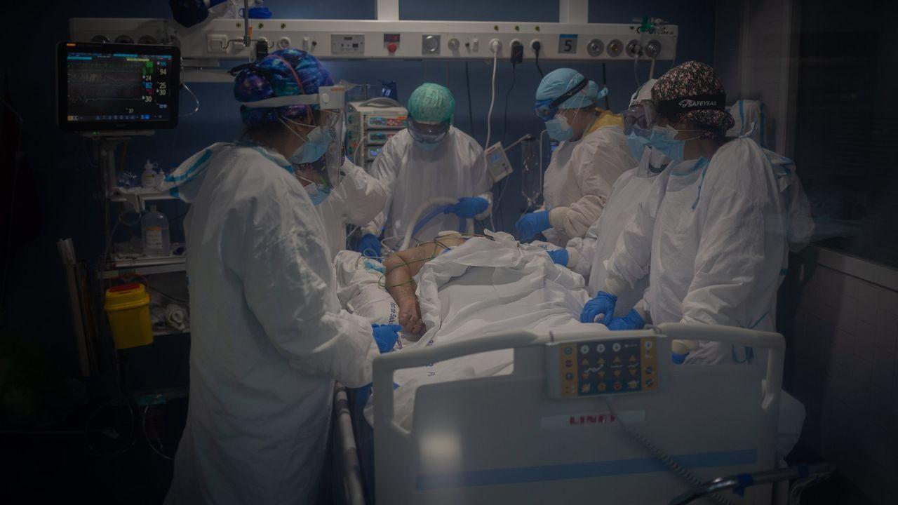 Trabajadores sanitarios protegidos atienden a un paciente en la Unidad de Cuidados Intensivos –UCI- del Hospital del Mar, en Barcelona