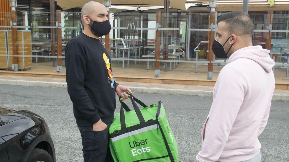 Luis Lobo (a la derecha), junto a otro repartidor de comida al inicio de la jornada de ayer