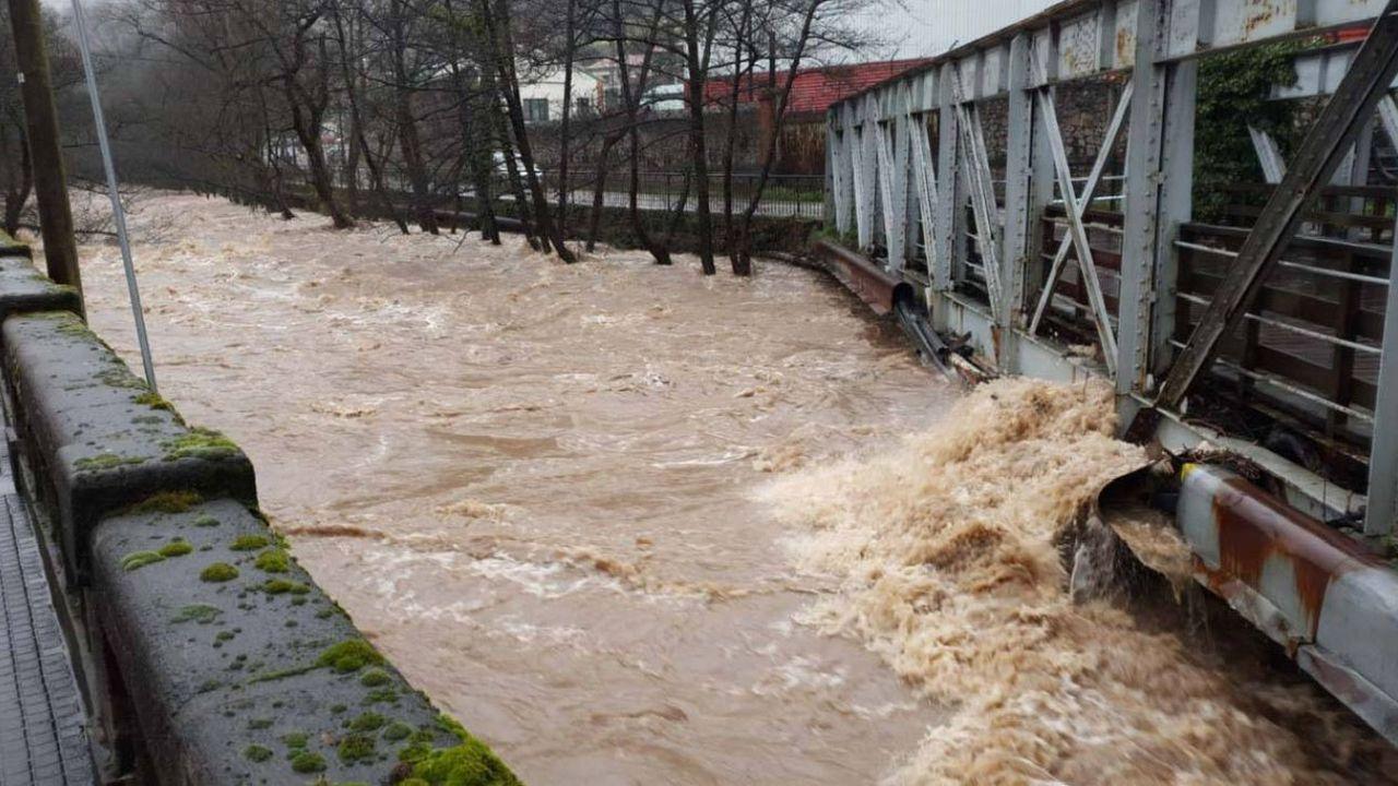 Crecida del río Trubia a su paso por un puente peatonal