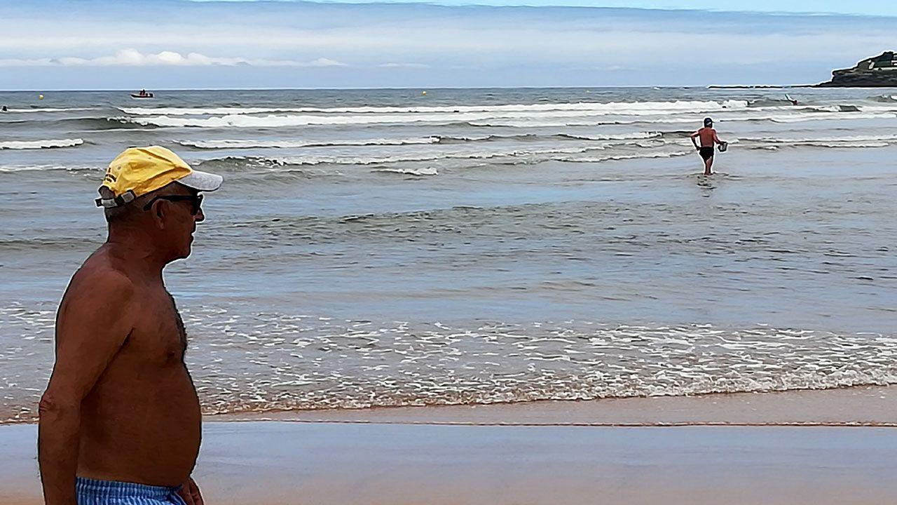 Un paseante y un bañista en la apertura de la temporada oficial de baños en la playa de San Lorenzo