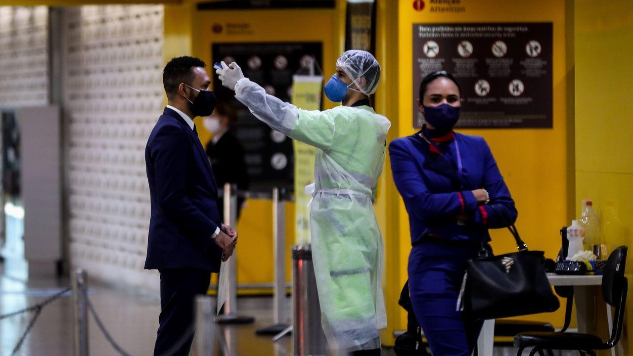 Personal de salud toma la temperatura a los que ingresan a una zona de embarque en el aeropuerto internacional de Guarulhos este lunes, en Sao Paulo (Brasil)