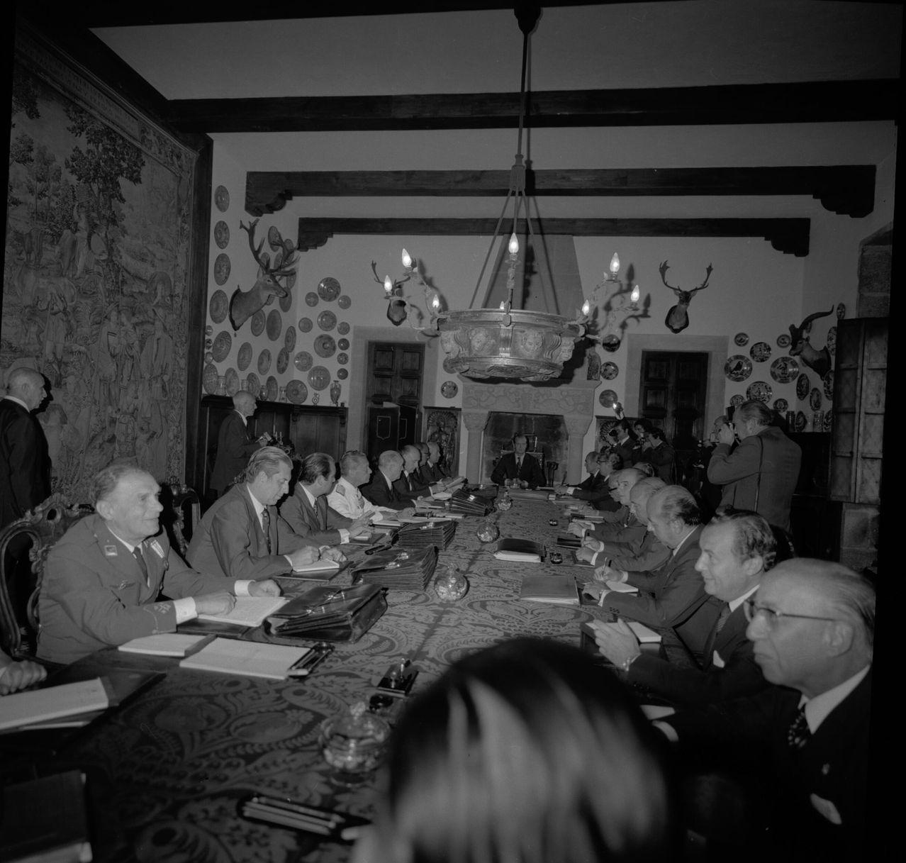 Consejo de ministros presidido por el entonces príncipe Juan Carlos en una de las estancias del pazo, en la que se aprecia un tapiz cubriendo una de las paredes, trofeos de caza y una de las chimeneas monumentales de la planta baja