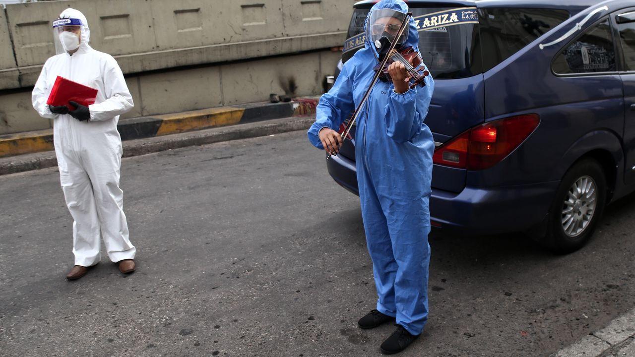 Un violinista con traje de protección toca su instrumento durante el funeral de una víctima de coronavirus en Bogotá, Colombia