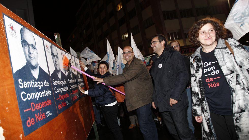 Rubén Cela, del BNG, pega el cartel electoral de su partid en Santiago