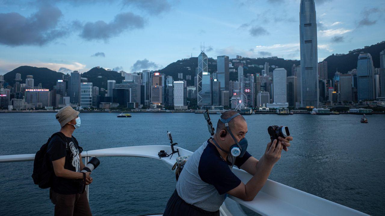 Un fotógrafo utiliza una mascarilla mientras que saca fotos en Hong Kong, China