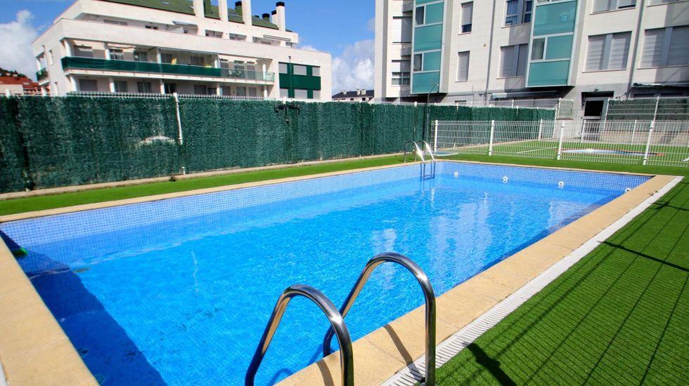 Vista de la piscina y los pisos de Luanco