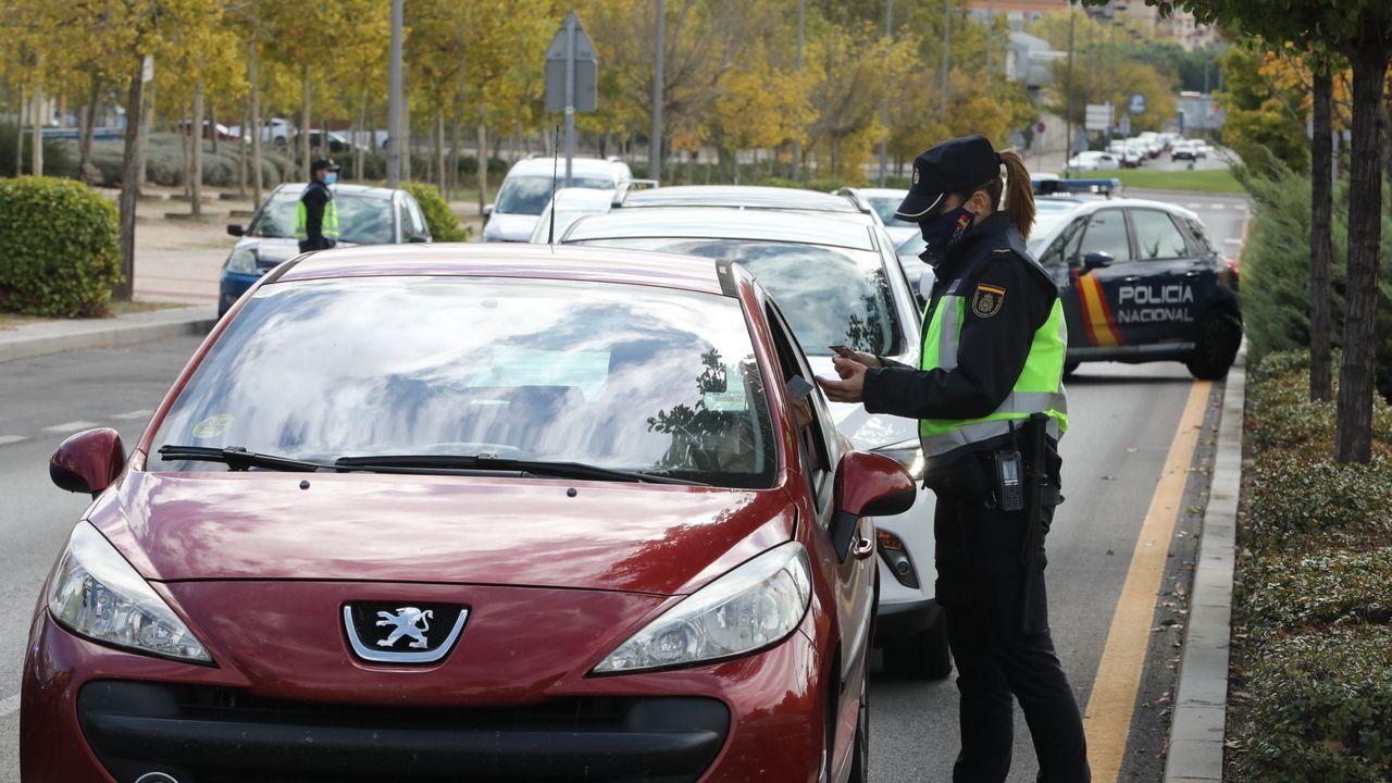 Una agente de la Policía Nacional comprueba la documentación de un conductor durante un control policia de las restricciones de movilidad en el municipio madrileño de Alcorcón, Madrid (España)