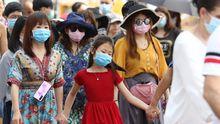 Turistas extranjeros se tapan con máscaras contra el coronavirus durante una visita al templo del Buda Esmeralda, en la ciudad tailandesa de Bangkok