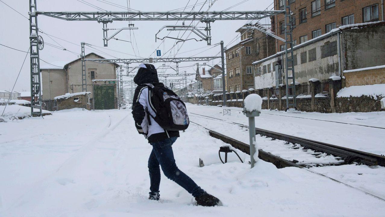 El Bng denuncia la falta de conexiones y frecuencias ferroviarias de Lugo.Una persona cruza las vias del tren, en la localidad cántabra de Reinosa, cuya comunidad se encuentra en alerta roja por nieve lo que está complicando el tráfico en gran parte de la región y en las conexiones con la Meseta y con Vizcaya, por las nevadas pero también por el granizo que ha hecho su presencia