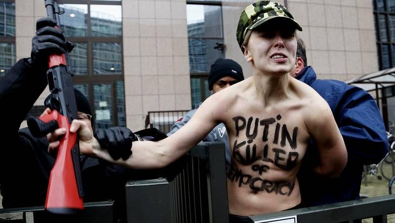 Graves enfrentamientos en Ucrania.Un manifestante come en una barricada mientras los antidisturbios montan guardia en las calles de Kiev, cuya ocupación transcurrió ayer sin incidentes.