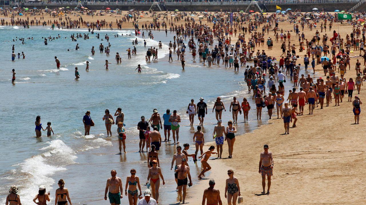 La playa de As Catedrais se vuelve a llenar de gente con mascarilla.Varias personas disfrutan de un soleado día de verano en la playa de San Lorenzo en Gijón,