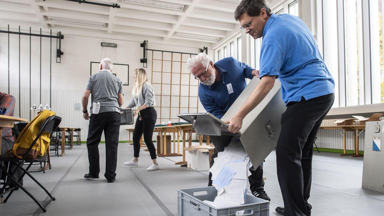 Voluntarios vuelcan las papeletas de una urna para inicar el recuento en las elecciones parlamentarias de Suiza