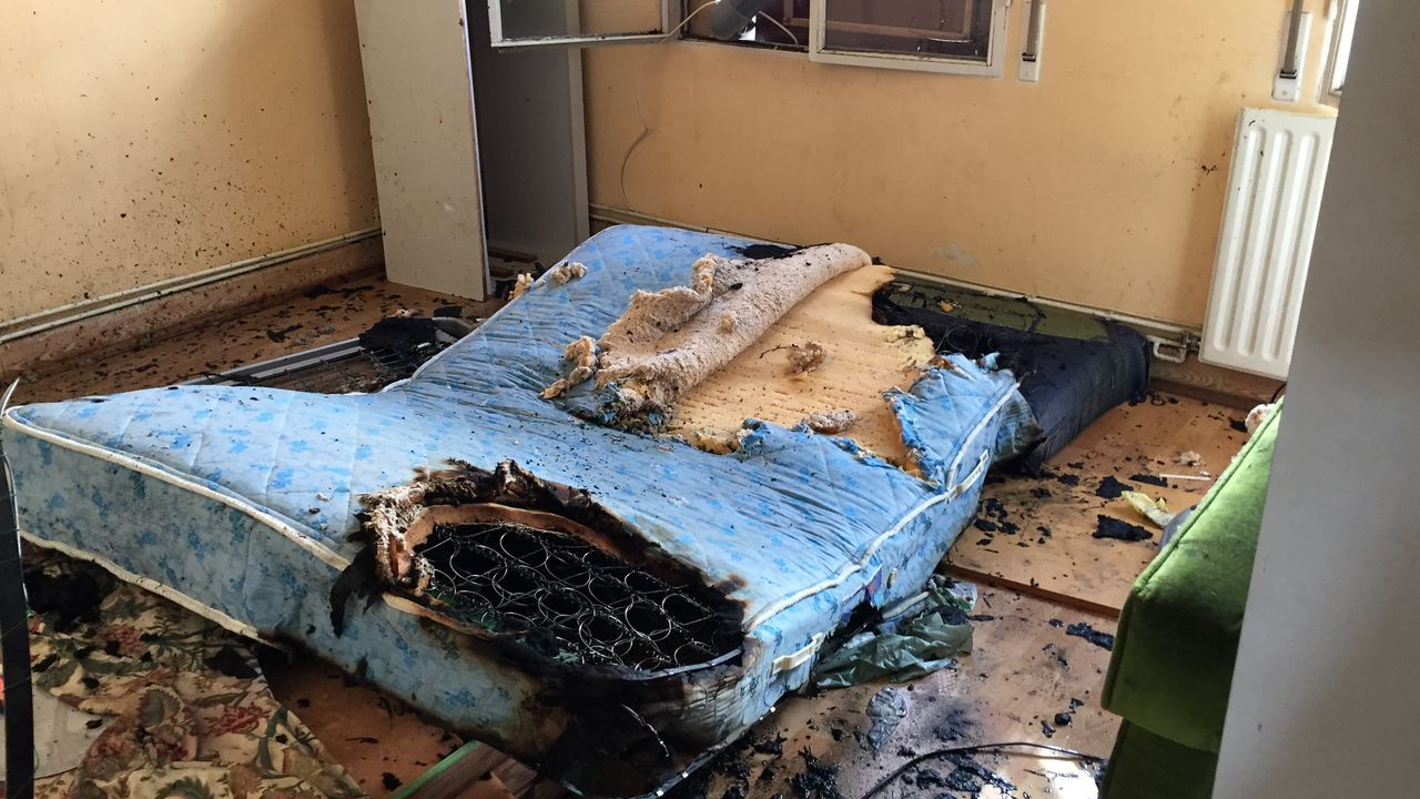 Una cama quemada en una de las habitaciones del piso okupado