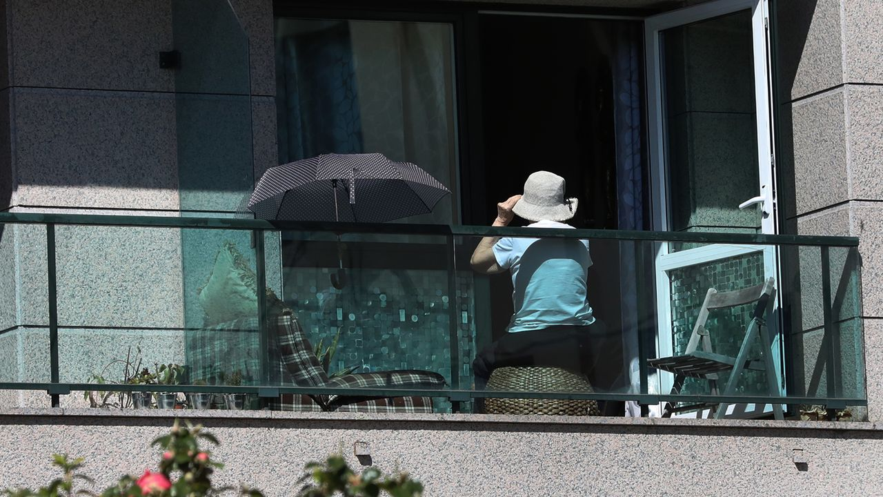 La compra en casa en Monforte con la Cruz Roja.Una mujer en un balcón en Santiago