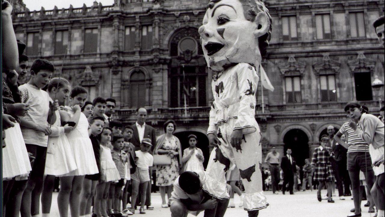 RETROSPECTIVA DE 1960 CON GIGANTES Y CABEZUDOS EN LAS FIESTAS DE MARIA PITA. UNO DE LOS NIÑOS ASISTENTE  AL ACTO LUDICO COLOCA EL CALCETIN A UNO DE LOS CABEZUDOS.