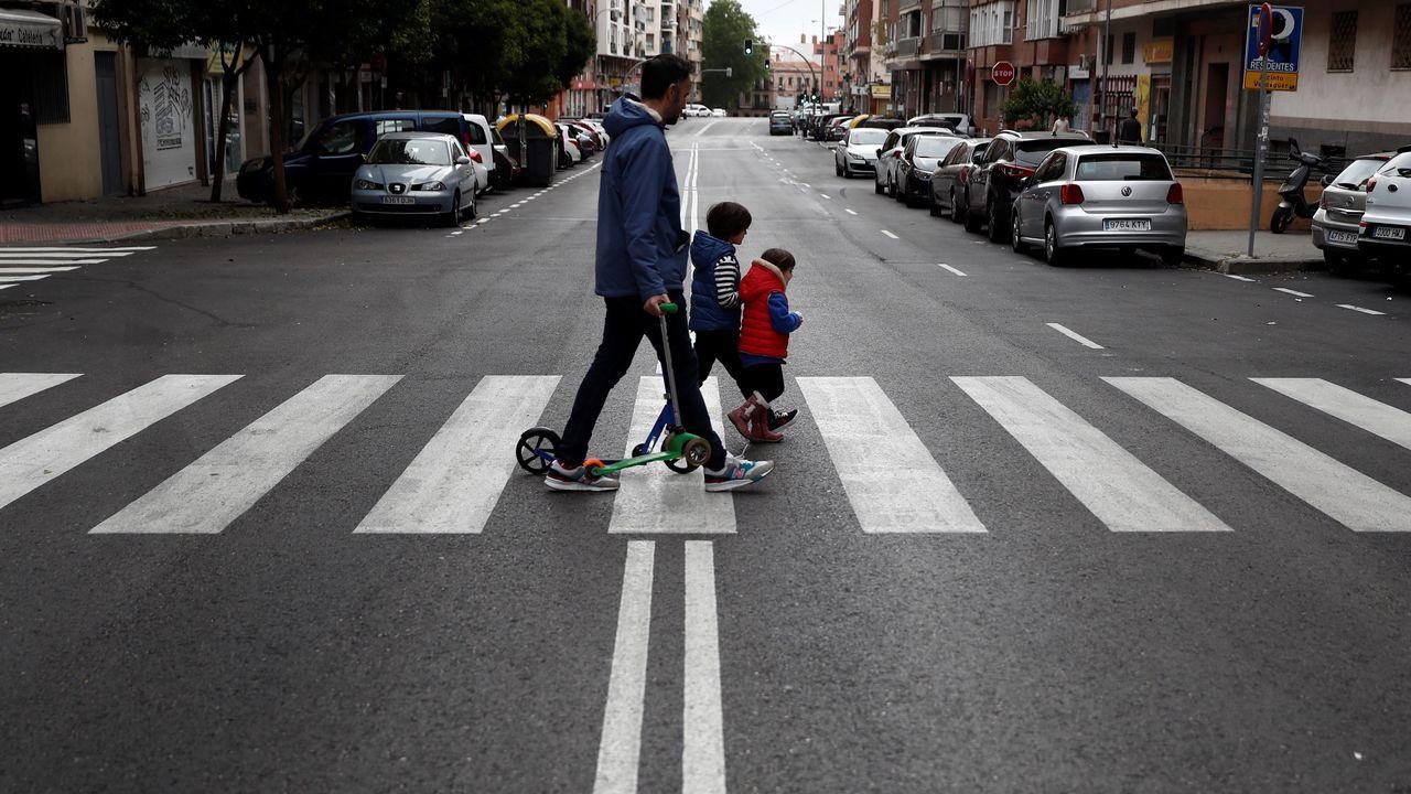 Dos niños acompañados cruzan una calle de Madrid este domingo
