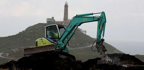 Una excavadora retira una de las zapatas de los aerogeneradores, frente al faro de Cabo Vilán.