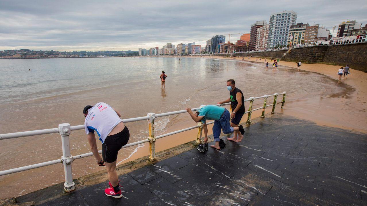 Varias personas en la playa de San Lorenzo de Gijón, en un día nublado