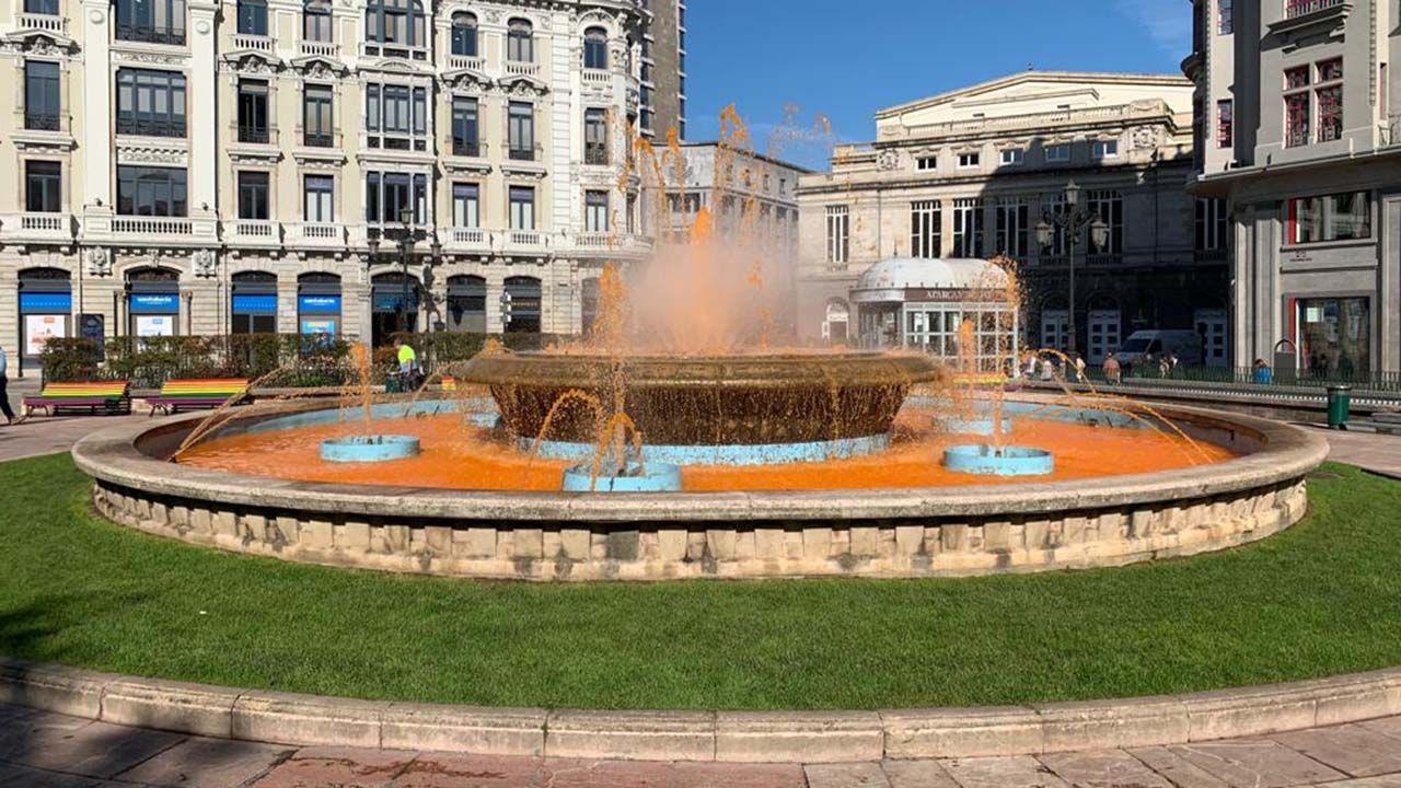 Central de servicios de la Policía Local de Gijón.La fuente de la plaza de La Escandalera se tiñe de naranja por el día mundial del ictus