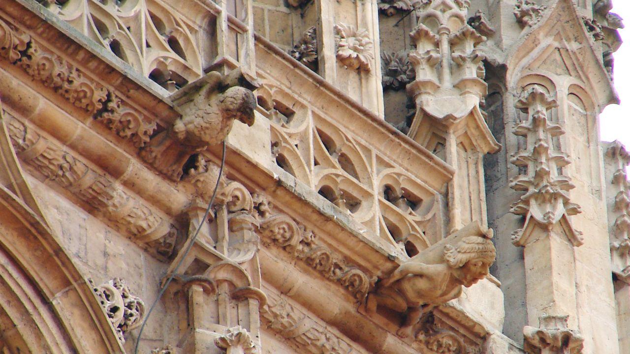 Un águila y una figura humana, gárgolas en la fachada de la Catedral de Oviedo. El águila vigila, mientras que el humano sufre bajo el peso del canalón y la cornisa en una postura forzada