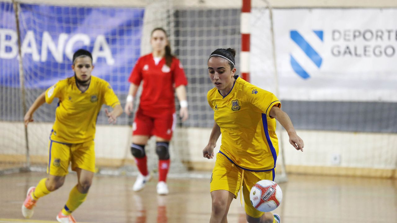 El equipo femenino de fútbol sala Burela Pescados Rubén golea al Móstoles.Dos burelistas pugnando por el balón con un zaragozista, en el partido de este sábado