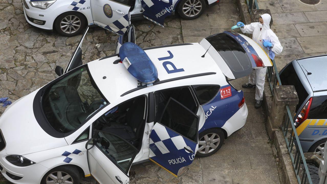 En una foto de archivo, policías locales de Santiago higienizan sus vehículos