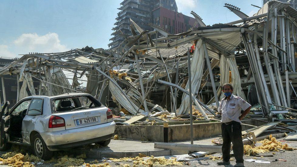 Un guardia de seguridad delante de la sala de exposición de Audi Motor destruida por la explosión