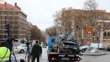 Una grúa municipal traslada un coche dañado por los cascotes de la explosión de ayer en la calle Toledo, en Madrid