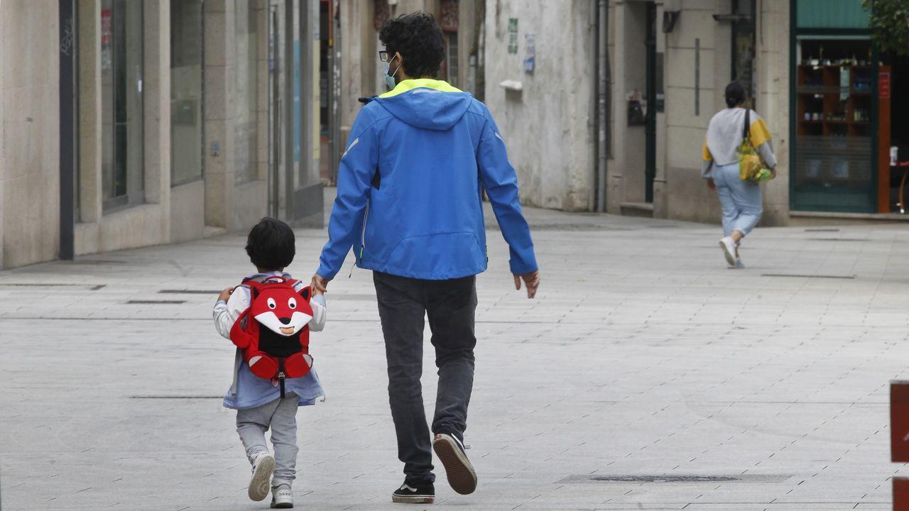 Imagen de archivo de un niño caminando con su padre tras salir del colegio