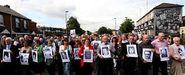Familiares y amigos de las víctimas del domingo sangriento se manifiestan en la plaza Guildhall, de Londonderry, con los retratos de los catorce asesinados