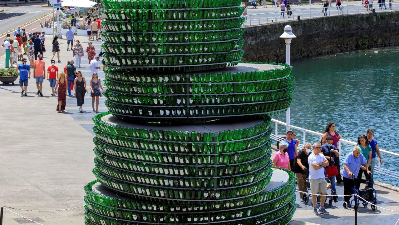 Gente camina cerca del Arbol de la Sidra, escultura de casi 8 toneladas de peso, en el Puerto Deportivo de Gijón, en la construcción se emplearon 3.200 botellas de vidrio verde