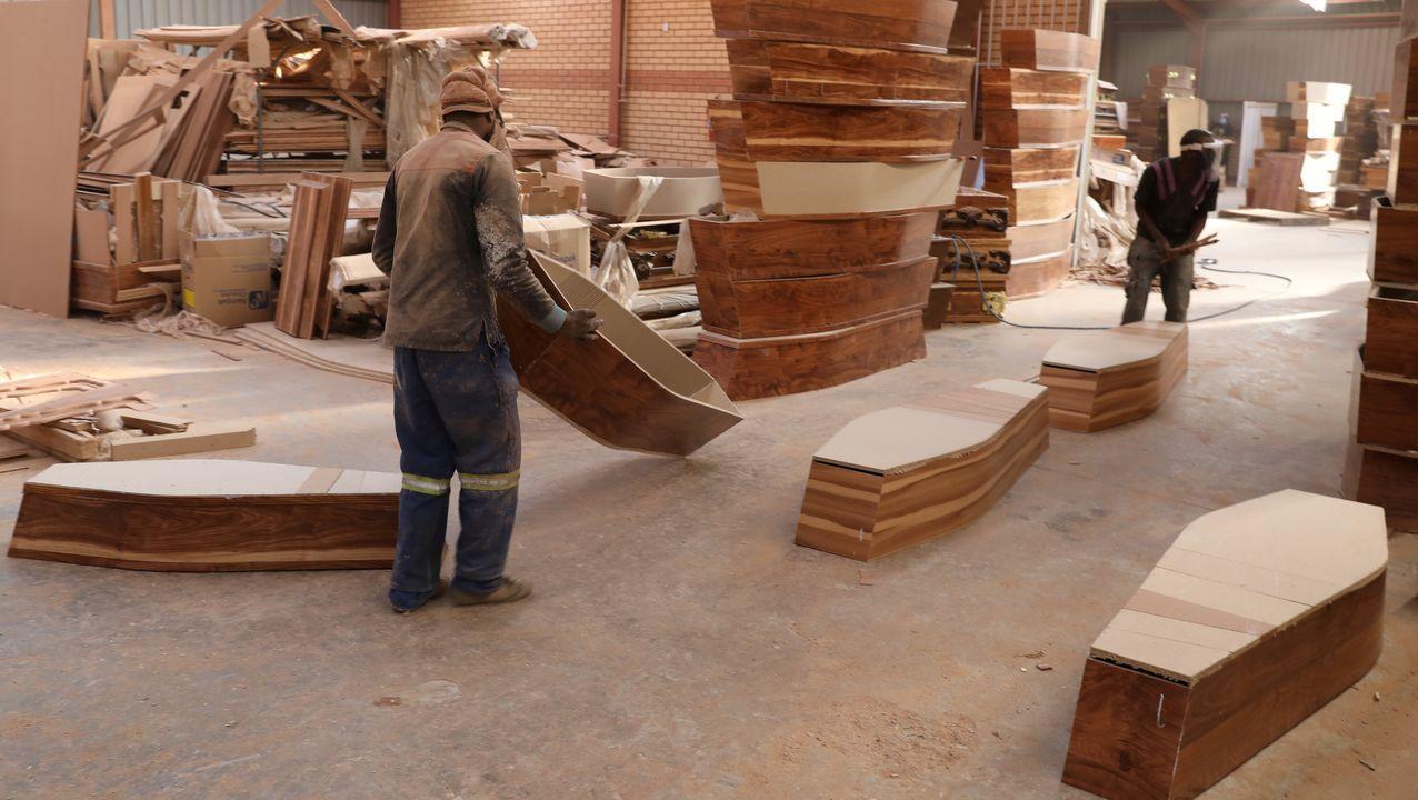 Un trabajador lleva un ataúd en una planta de fabricación, en Johannesburgo