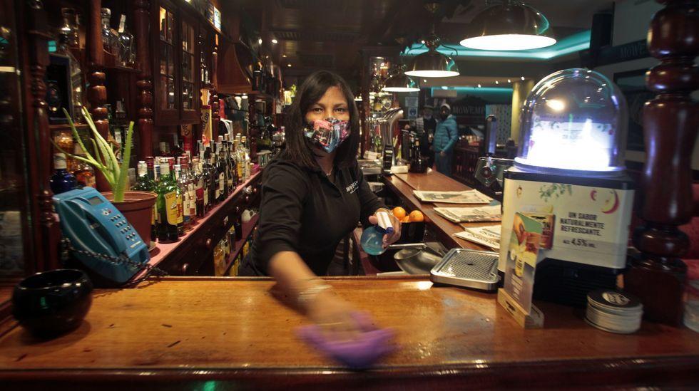 Una camarera limpia la barra en una cafetería de Monforte