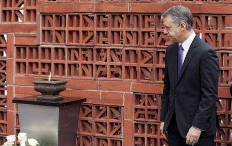 Urkullu, ante el pebetero instalado en la entrada al Parlamento vasco en recuerdo a las víctimas.
