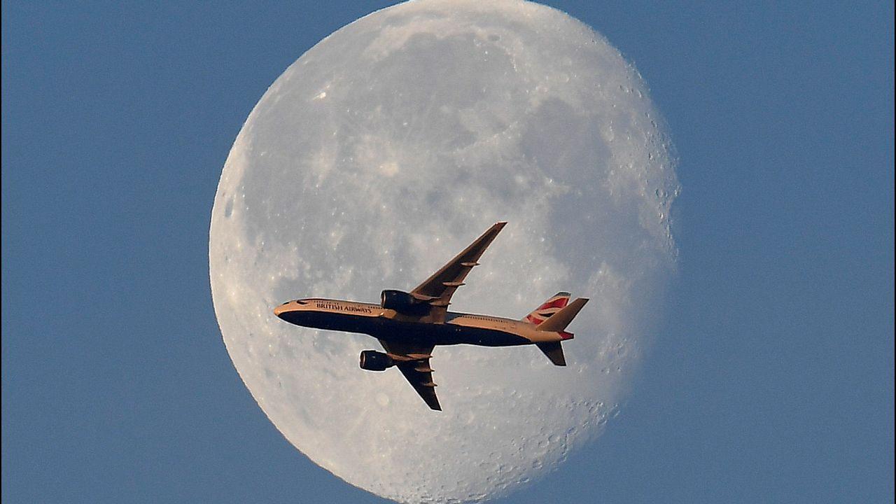 Un avión de pasajeros de British Airways vuela frente a la luna sobre Londres