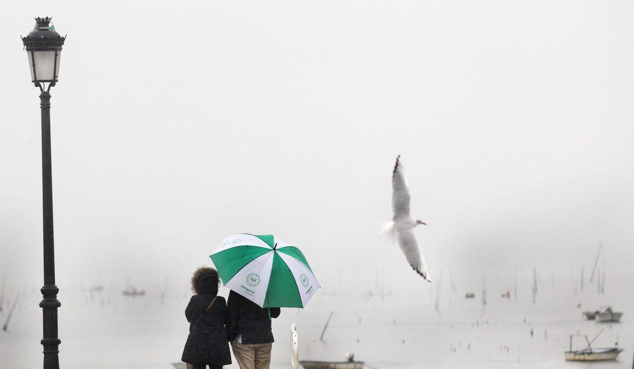 Pareja paseando en un día de lluvia y niebla en Vilagarcía de Arousa