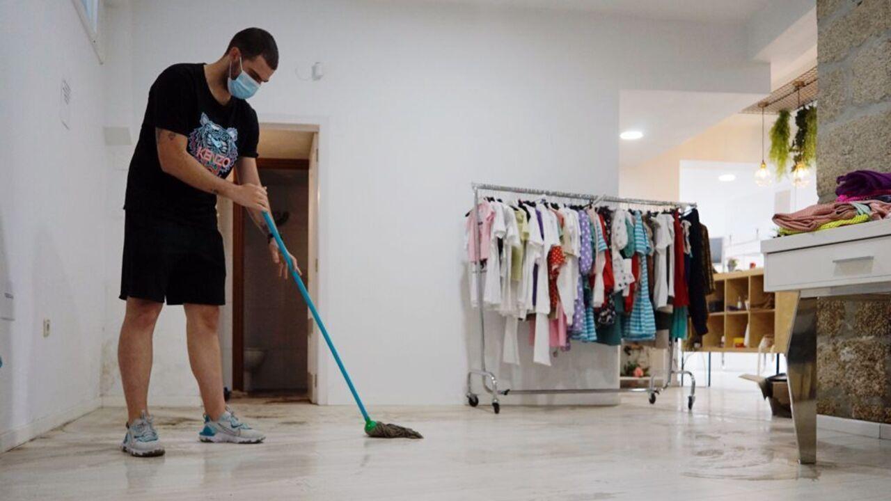 Guillermo Blanco, de la tienda de ropa Xeitos, limpiando el local tras las inundaciones