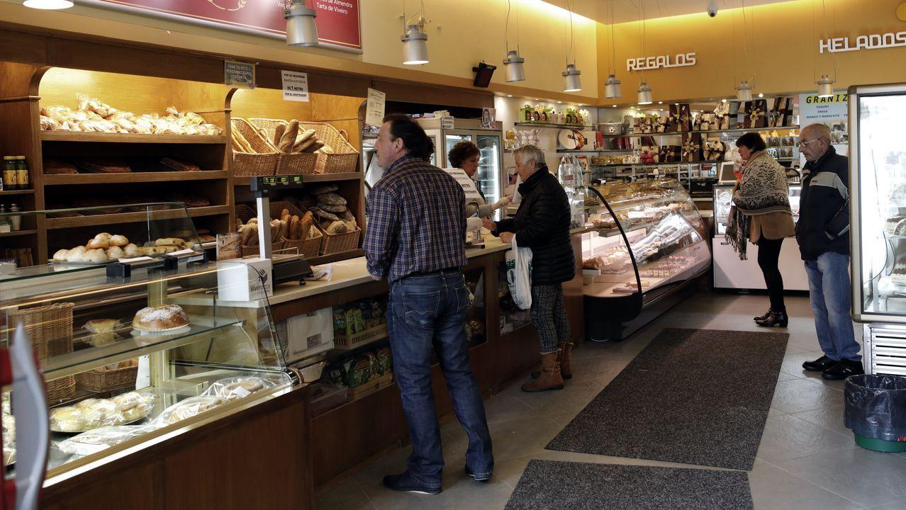 Cuatro personas, separadas entre ellas, haciendo compras en una pastelería