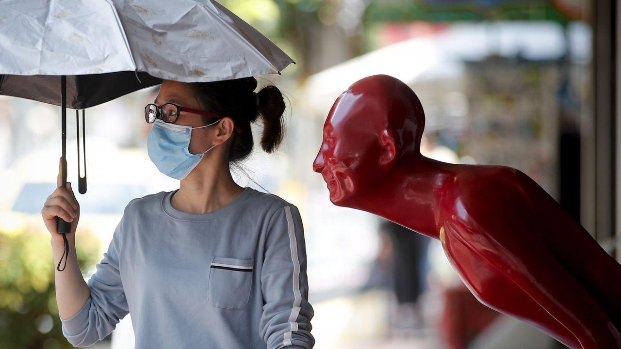 Una mujer, con máscara en una calle de Bangkok, en Tailandia