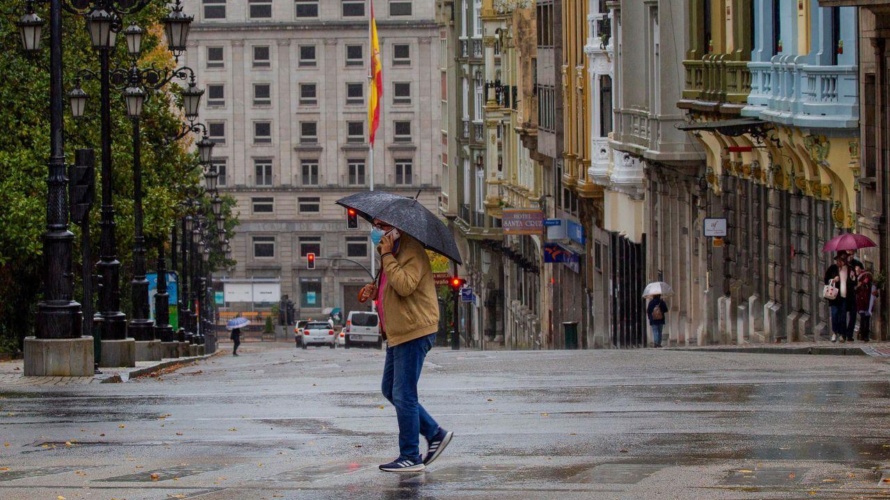 Un hombre camina bajo la lluvia en el centro de Oviedo