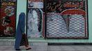 Una afgana pasa por una tienda de Kabul con una publicidad con el rostro de una mujer borrado.