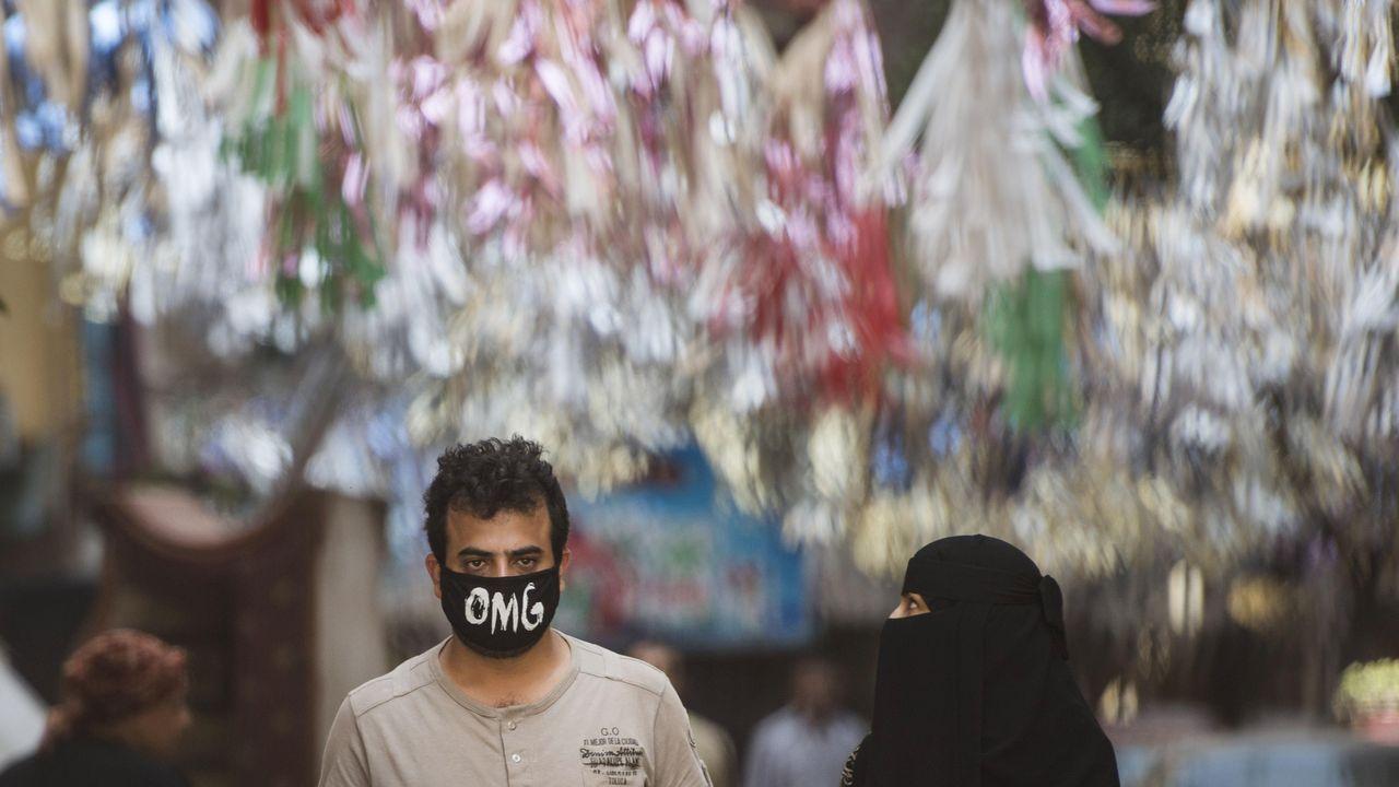En El Cairo, un hombre lleva una máscara facial que dice «oh dios mío» en inglés