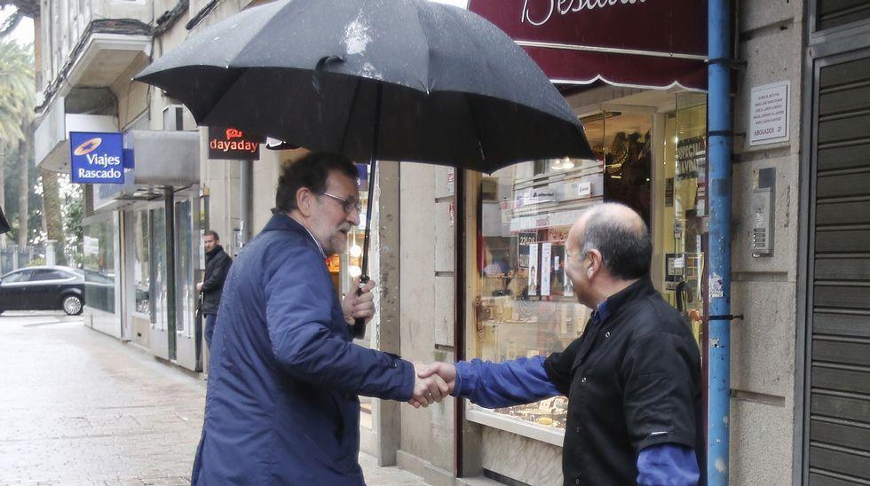 El político pontevedrés tuvo que protegerse de la lluvia que azotaba Galicia